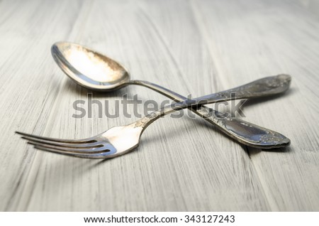 old cutlery on white wooden table in different positions