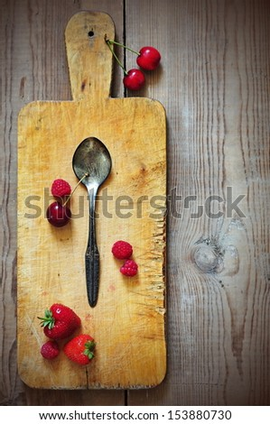Old cutting board with silver spoon and some fruits on wooden table - stock photo