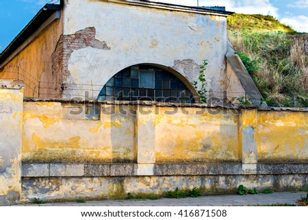 old damaged yellow plastered brick wall with a barred window, pavement
