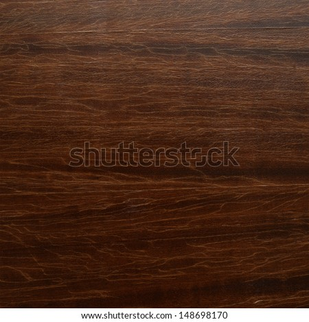 Old dark brown varnished wood with a cracked lacquer fragment as a background - stock photo