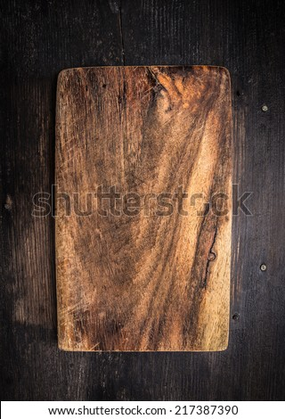 Old dark cutting board on brown wooden table, background - stock photo