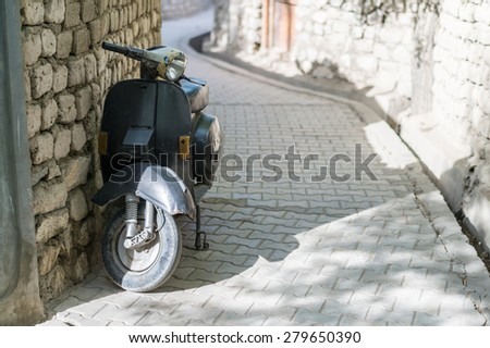 Old dark grey scooter parked by the wall on empty street. - stock photo