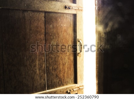 Old dark room with shining closed door. - stock photo