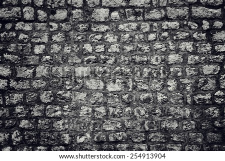 Old dark stone wall background - stock photo