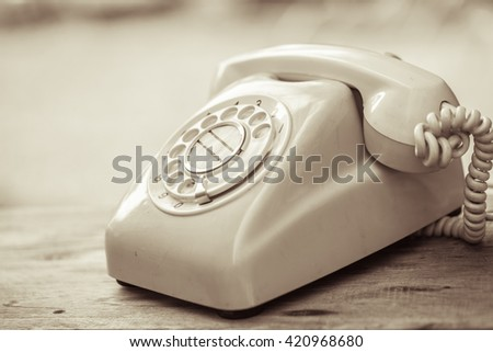 old day phone or rotary telephone on wood table vintage color tone - stock photo