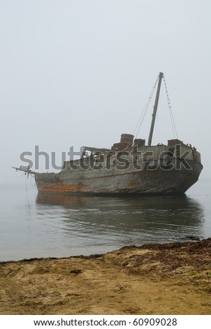 Old decayed burned and sunken boat by the sandy shore of the sea in the fog - stock photo