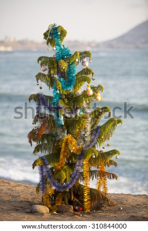 Old decorated christmas tree standing by the beach with ocean in Miraflores. Lima - Peru - stock photo