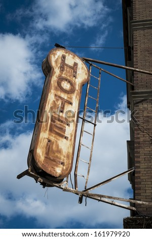 Old, decrepit, weathered sign for a hotel - stock photo