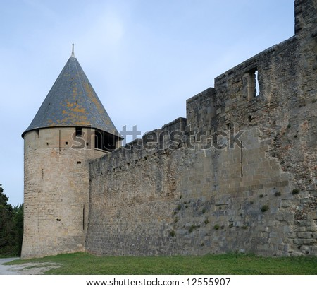 Old defense stone wall recovered with rough masonry and conic tower of Carcasson castle in sunlight against blue sky, France