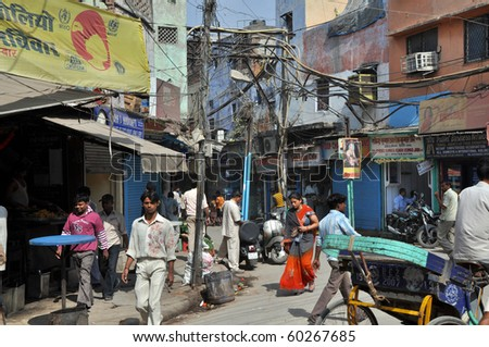 OLD DELHI, INDIA -OCTOBER 24:People travel under the risky and chaotic electrical wiring on October 24, 2009 in Old Delhi. Unsatisfying condition of wiring causes power problems in Delhi. - stock photo