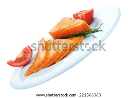 old delicious cheddar cheese chop with slice on blue plate with tomatoes and chives isolated over white background