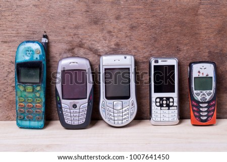 Old design collection of cell phones isolated on wood background