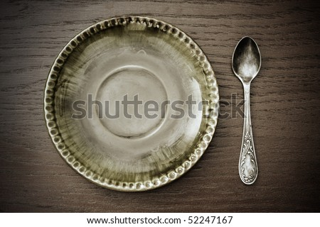 old dessert plate and spoon - stock photo