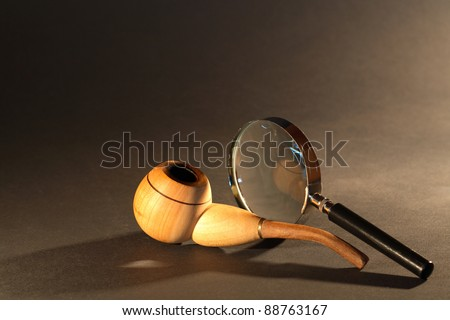 Old detective concept. Magnifying glass and tobacco pipe on dark surface - stock photo