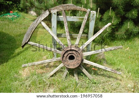 Old devastated wooden wagon wheel standing in garden