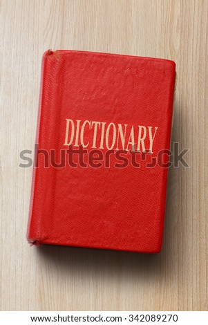 Old dictionary in closeup on the wooden background