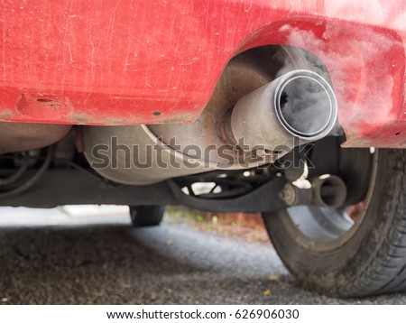 Old diesel car exhaust detail, with fumes. Now deemed environmentally unfriendly. Visible soot.