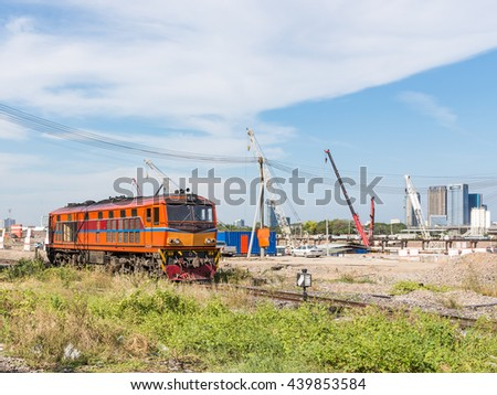 Old diesel electric locomotive is passing the construction site near the urban station. - stock photo