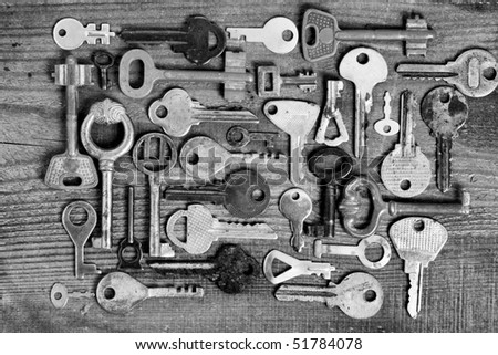 Old different keys on wooden board (black and white) - stock photo