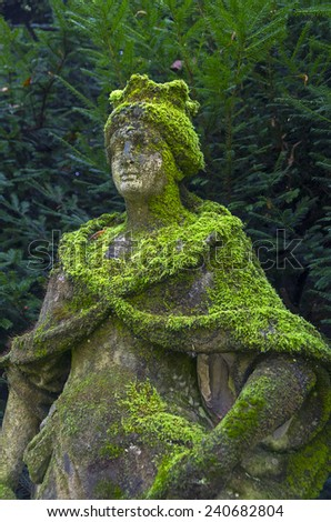 Old, dilapidated and moss-covered statue of Queen in Italian park. - stock photo