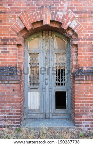 Old dilapidated door in masonry house front - stock photo