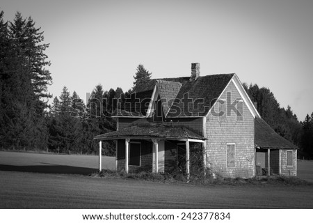 Old dilapidated house in a nicely moved grass field in the Fraser Valley of British Columbia in black and white