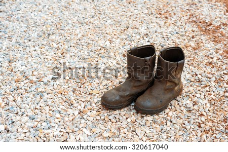 old dirty boots.old boots worn with scratches and untied shoelaces on rock background - stock photo