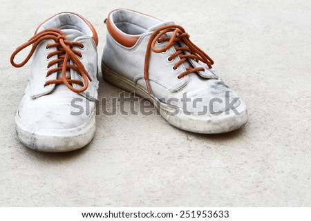 old dirty brown sneaker on gray background