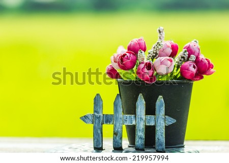 old dirty fake rose on wood table - stock photo