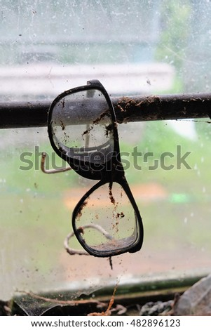 old dirty glasses to protect the eyes hanging on the window of an abandoned barn. rural life.
