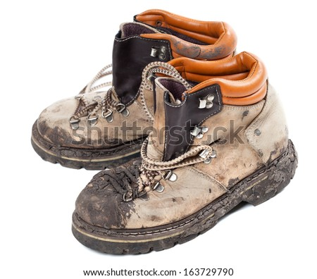 Old dirty hiking boots isolated on white background - stock photo