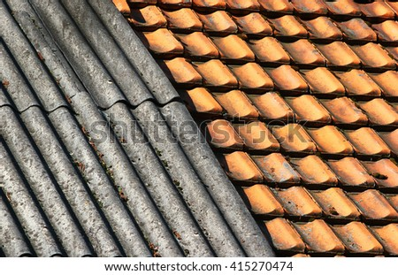 Old dirty weathered wavy slate and ceramic tiles shingle roof background. - stock photo