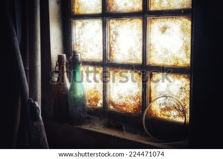 Old dirty window with dusty bottles on the sill  - stock photo
