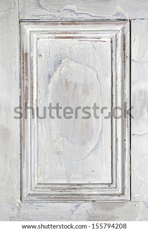 Old distressed wood door panel with peeling paint as framed background - stock photo