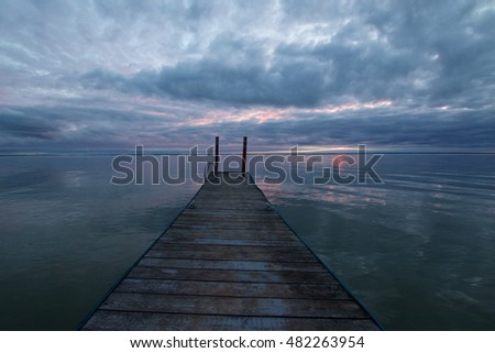 Old dock on lake in silhouette against moody clouds at sunset.