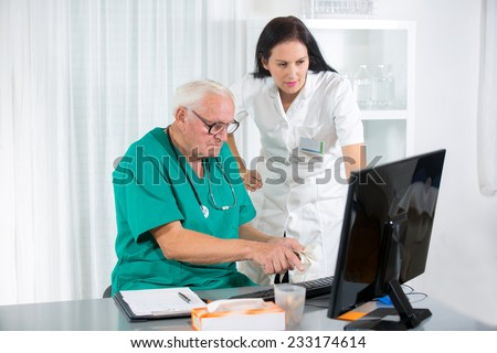 Old doctor and a nurse are consulted - stock photo