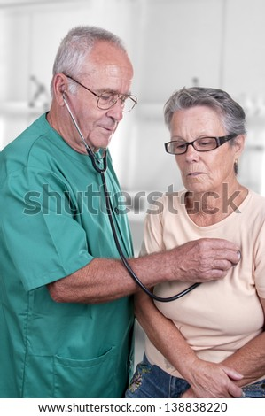 old doctor examining his patient - stock photo