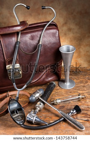 Old doctor's bag and collection of antique medical instruments such as stethoscope, reflex hammer and head mirror - stock photo