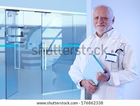 Old doctor standing in front of MRI room at hospital, holding tablet, smiling. - stock photo