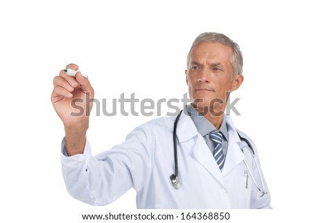 Old doctor writing with marker on invisible surface. Standing isolated on white