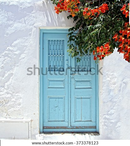 old door and white plastered wall on a greek Island in the sun