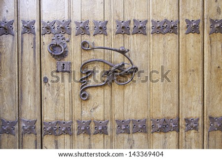Old door handle, detail of an ancient decorated handle in town, vintage, decoration - stock photo