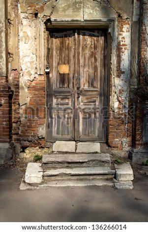 Old door in a crumbling building - stock photo