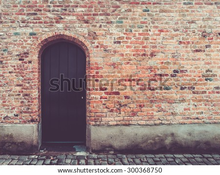 Old door in rustic brick wall, bruges, belgium - stock photo