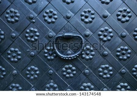 Old door knocker (medieval black iron door background) - stock photo