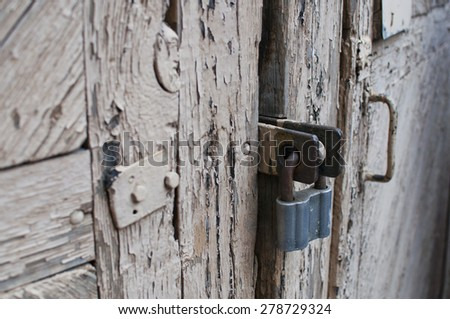 Old door made of wooden planks and rusty padlock