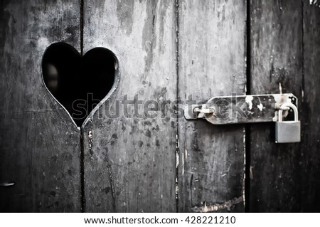 Old door with a heart padlocked - stock photo