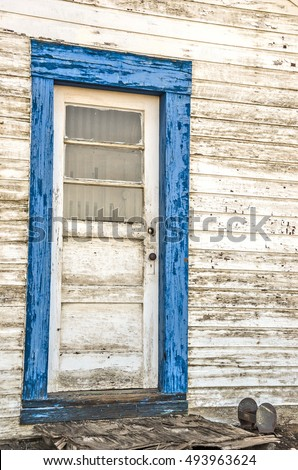 Old door with three windows framed with blue peeling paint that is covering green paint and loads of texture