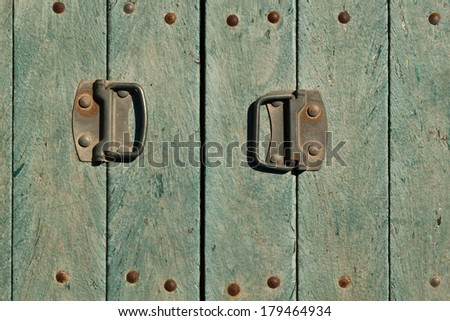 Old doors with the sun scorched paint and two handles covered with rust