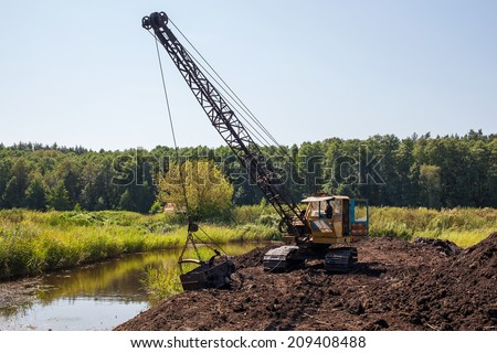 Old dragline (excavator) on the peat quarry in the swamp - stock photo